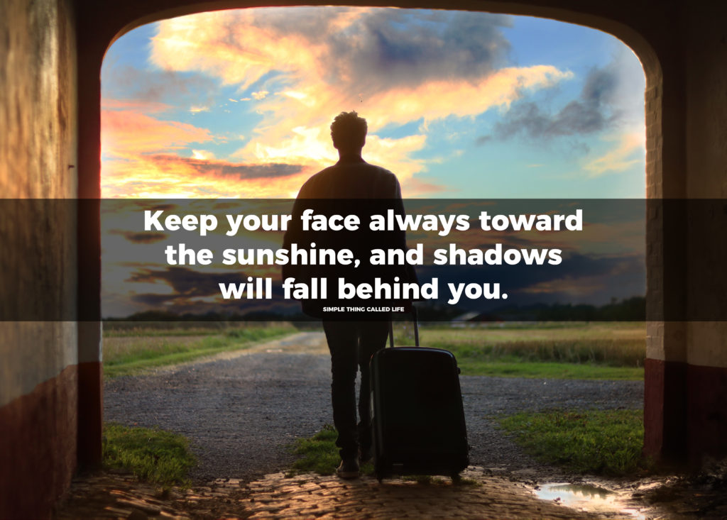 """A picture of a woman walking towards the sunlit path with a suitcase in tow, and the quote """"Keep your face always toward the sunshine - and shadows will fall behind you"""" overlayed on top of the picture."""