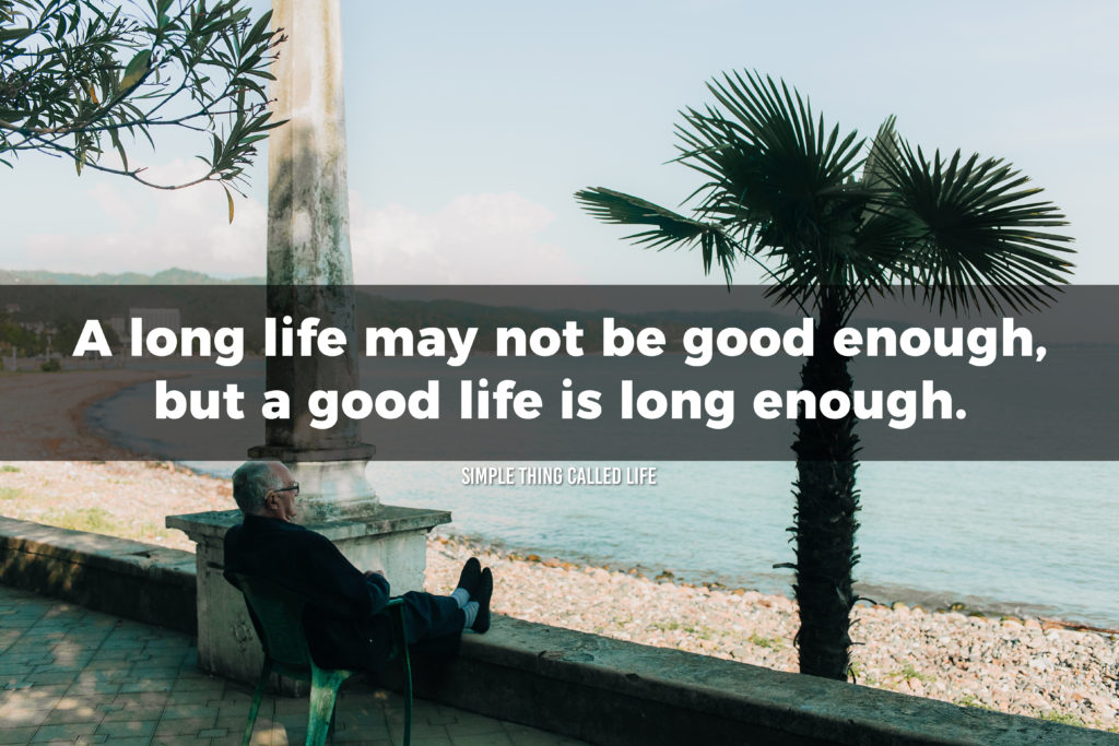 """An old man sitting in a chair with his feet up looking out over the beach, with the quote """"A long life may not be good enough, but a good life is long enough"""" overlayed"""